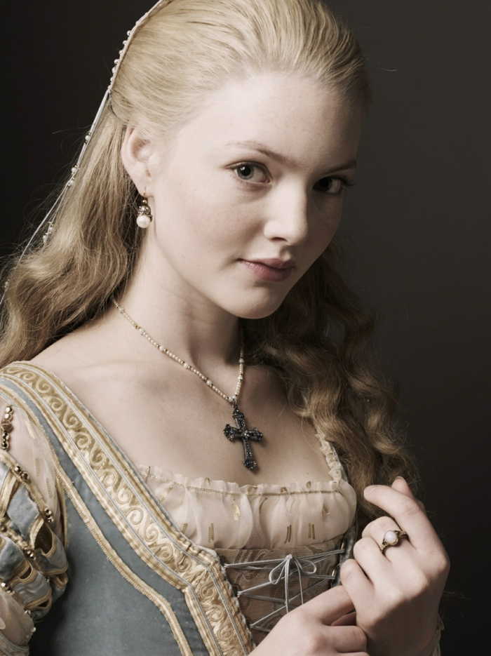 elizabethan hairstyles, blonde young woman, with hair tied back at the top, and let to fall in curls at the bottom, wearing renaissance dress, and a crucifix necklace
