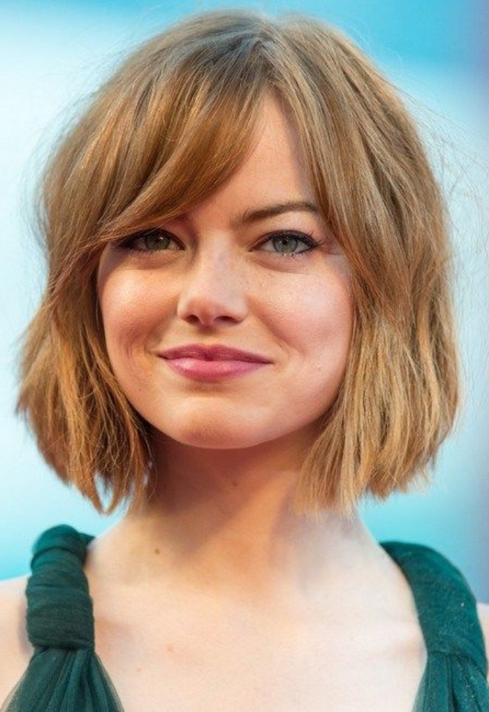 emma stone with a copper colored shaggy bob, and side bangs, wearing a top with green straps