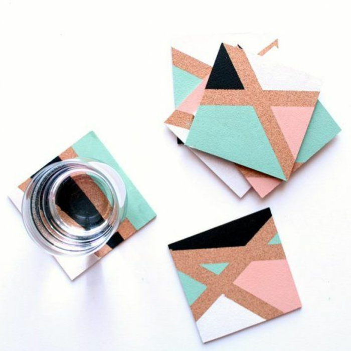 square cork coasters, decorated with asymmetrical blue and pink, and black and white shapes, diy craft projects, one clear glass