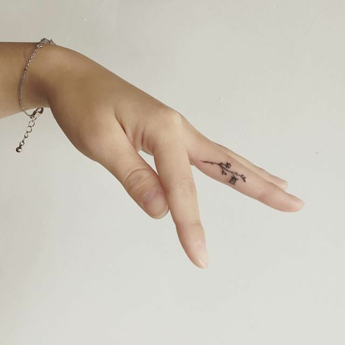 wildflower tattoo, close up of a female hand, with delicate silver bracelet, a tattoo of a tiny minimalistic flower, in black ink, on t6he side of her middle finger