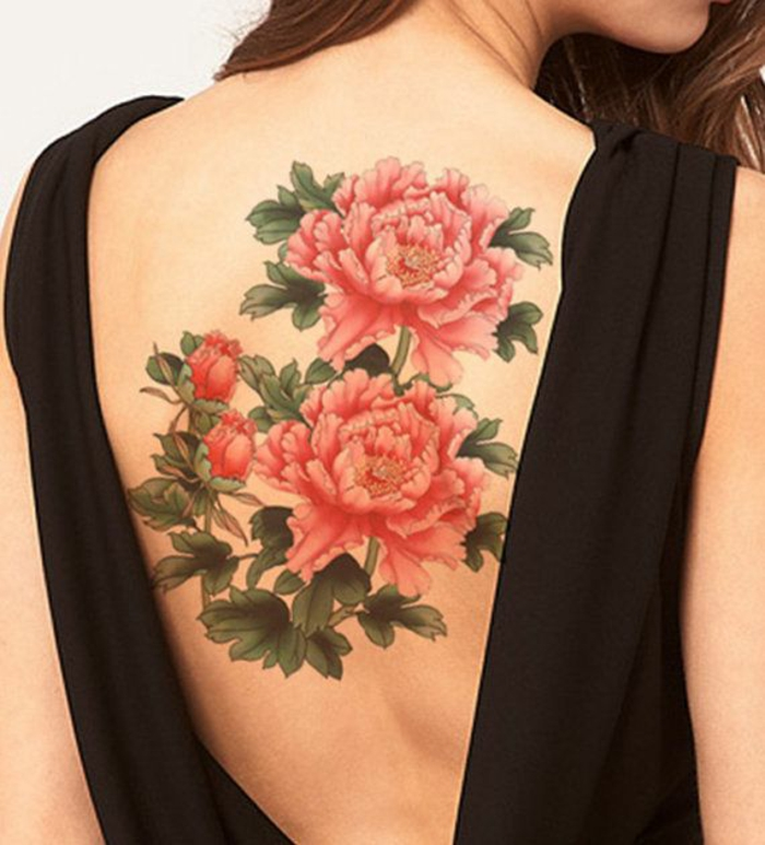 brunette woman wearing a black, open back top, revealing a large tattoo, of two blossoming pink-red peonies, with two buds and lots of green leaves