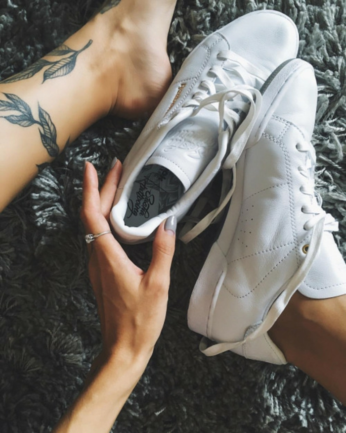 flower tattoos, close up on woman's feet and hand, one bare foot, with black ink leaf tattoos, other one in a white leather sneaker, hand holding other sneaker