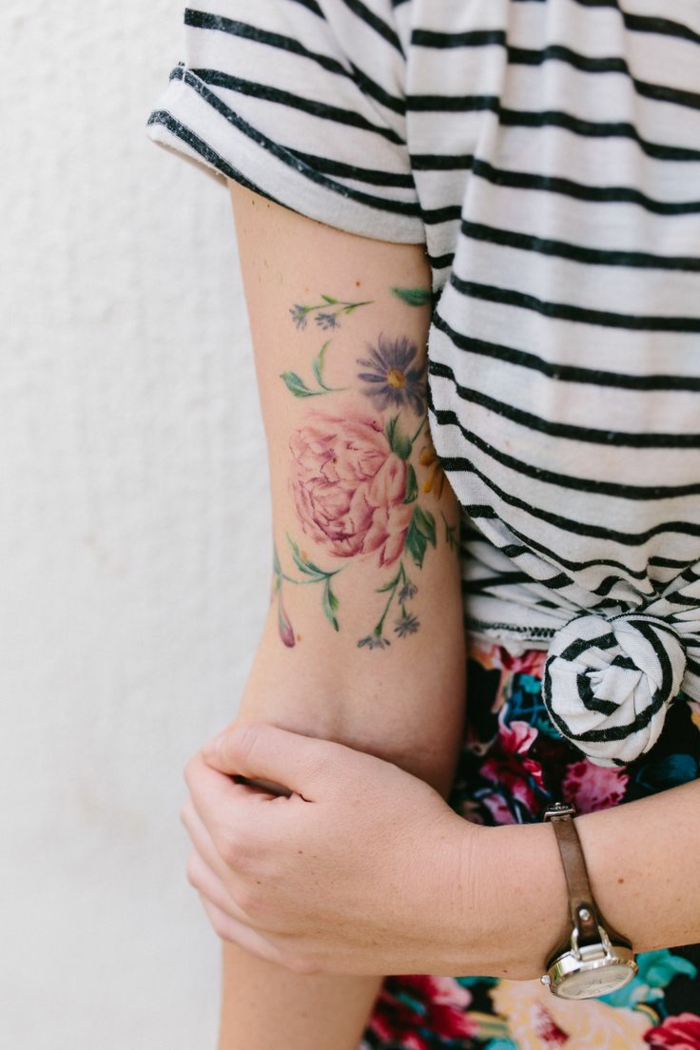 woman with black and white striped t-shirt, tied at the front, holding her arm, which has a colorful pink peony tattoo, with green leaves and blue, smaller flowers
