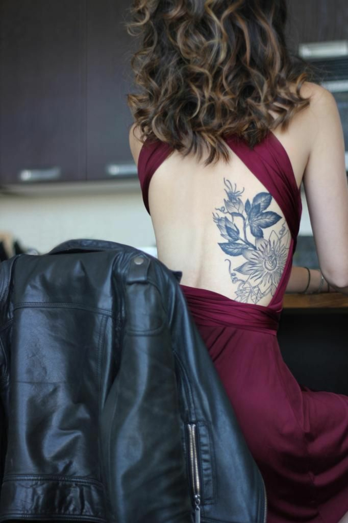 flower tattoos, woman with dark blonde curly hair, in burgundy dress with open back, with blue ink flower tattoo, on lower back, sitting on chair, near black leather jacket