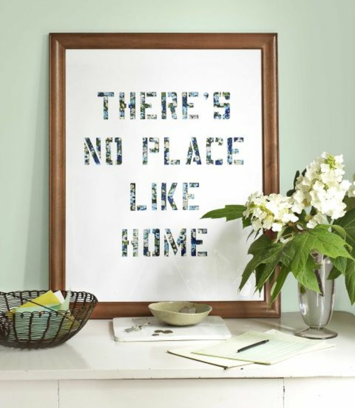 framed sheet of paper, with the words there's no place like home, homemade crafts, placed on a desk, near vase with flowers and stationary