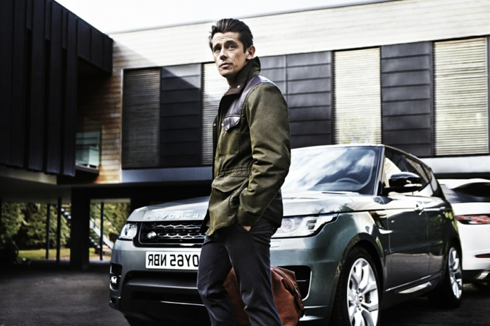 khaki winter jacket, with black leather details, combined with dark grey trousers, business casual outfits, worn by man holding brown travel bag