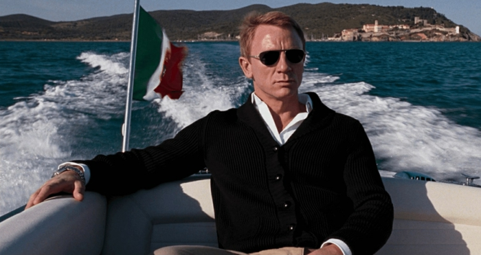 daniel craig with aviator sunglasses, business casual men, dressed in a black blazer, over white shirt, riding in a speedboat