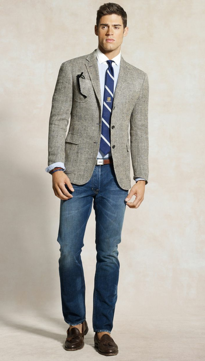 model wearing business casual jeans, with white shirt, blue and white striped tie, and grey blazer, brown leather loafers and belt