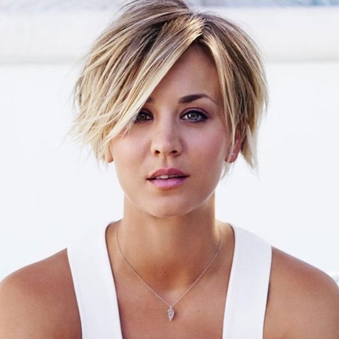kaley cuoco with a super short bob, side-parted and dyed blonde, with dark roots, wearing white tank top