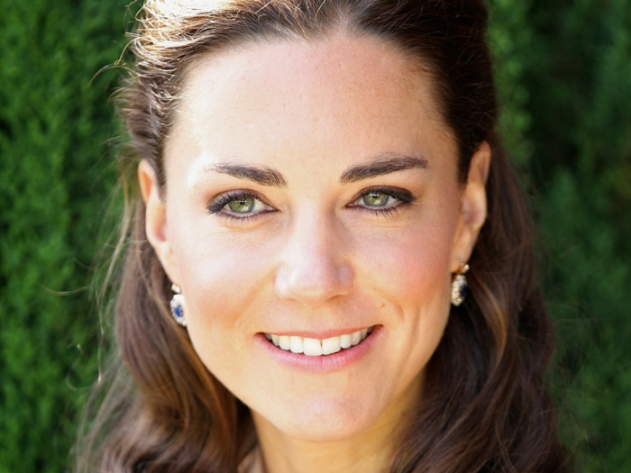 close up of kate middleton, natural brown wavy hair, tied back at the top, smile and green eyes, natural looking make-up, earrings with blue gems