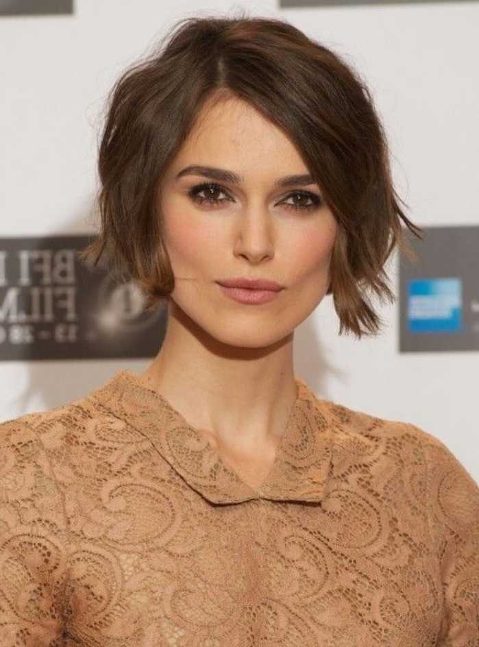 keira knightley with dark brunette, wavy short bob, and side parting, wearing nude-colored lace shirt