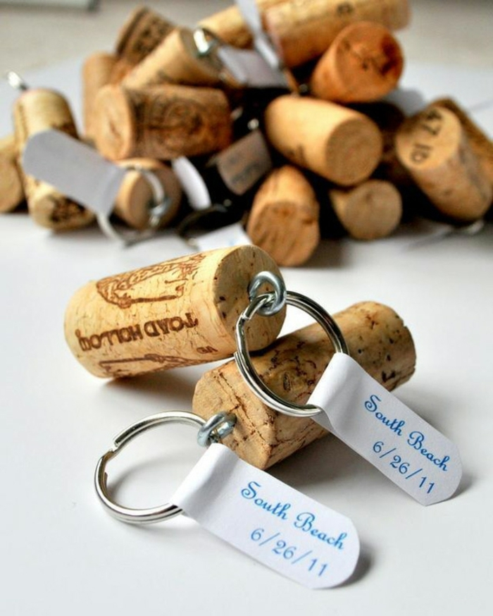 many keychains, made from cork bottle stoppers, and metal rings, decorated with white labels, marking a special ocassion, diy craft projects