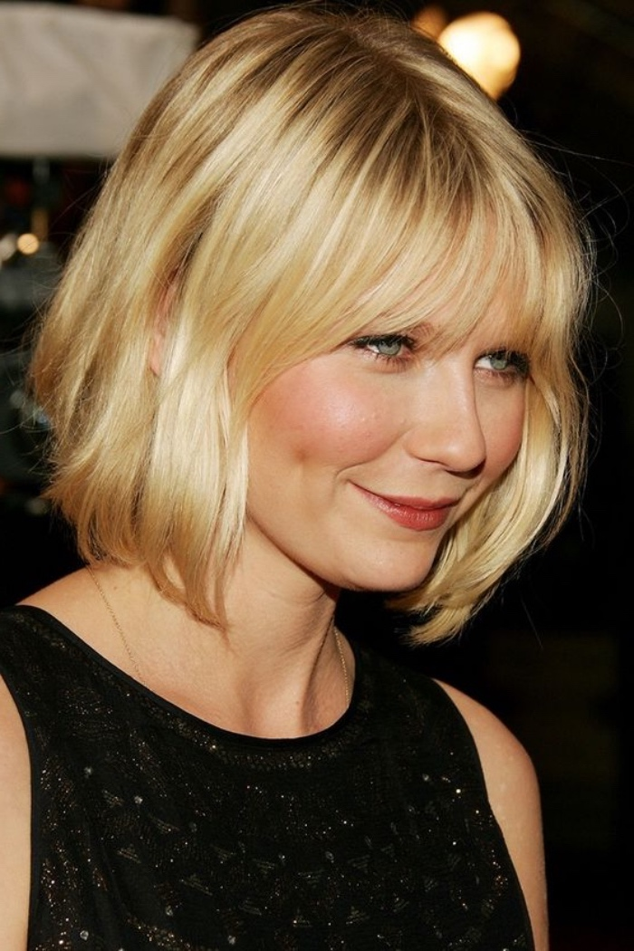kirsten dunst with blonde, wavy short bob, wearing black sleeveless glittery top