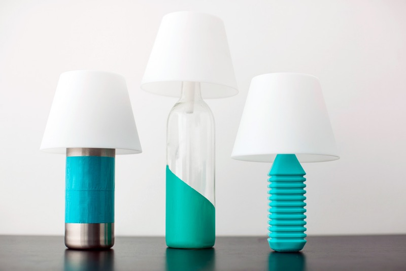 lamps made from three bottles, one silver colored with large blue stripe, one clear and partly dyed turquoise, and one plastic, fully died turquoise, with white lampshades