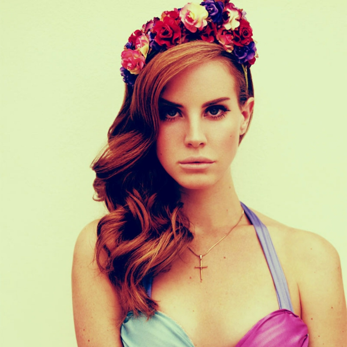 medieval hairstyles, red-haired lana del ray, with hairstyle inspired by the middle ages, curled and falling over one shoulder, and decorated with colorful flower crown