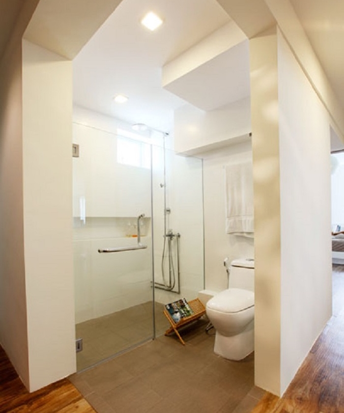 spacious semi-detached open plan bathroom, with thick white walls, containing large glass shower cabin, modern oval toilet seat, brown carpet and wooden floor
