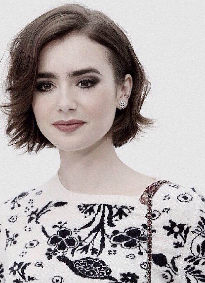 lily collins with chin-length wavy brunette hair, white sweater with black print, bob hairstyles