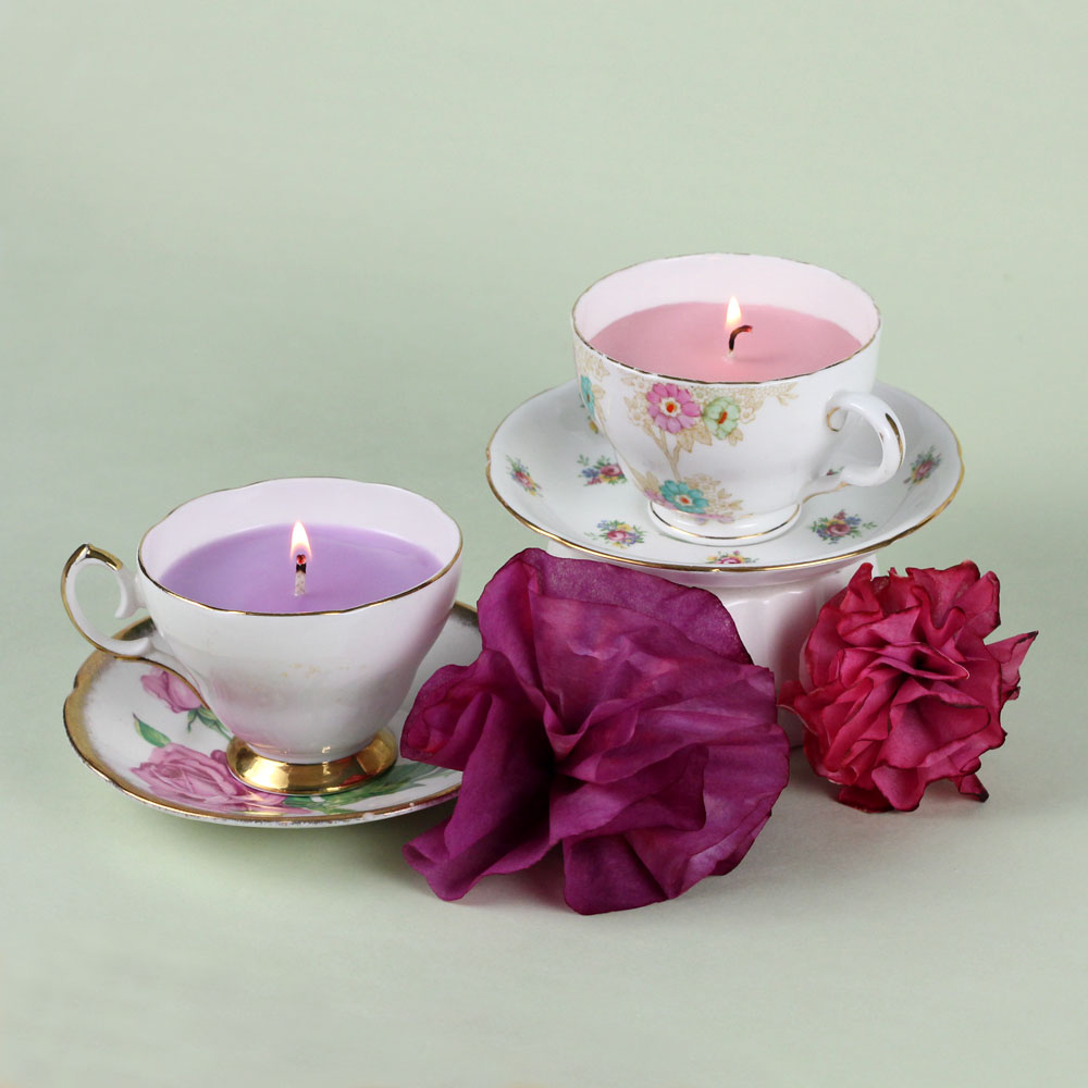 lit candles in pale pink and violet, inside porcelain tea cups, placed on saucers, fun and easy crafts, two purple flower ornaments nearby