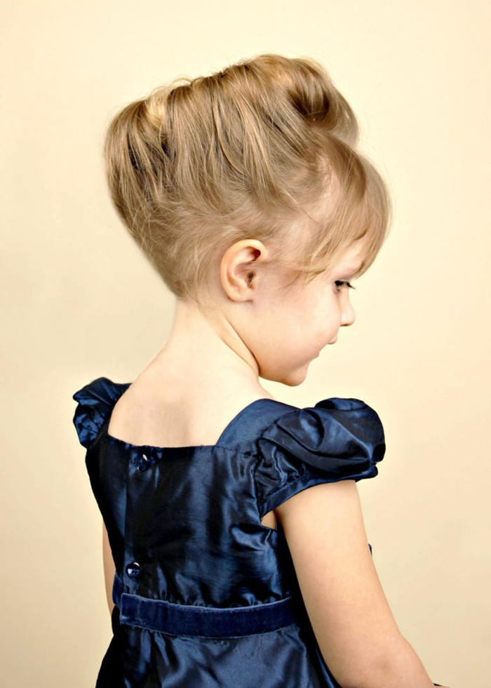 small blonde girl, with hair styled in renaissance-like hair bun, wearing a shiny, dark blue dress