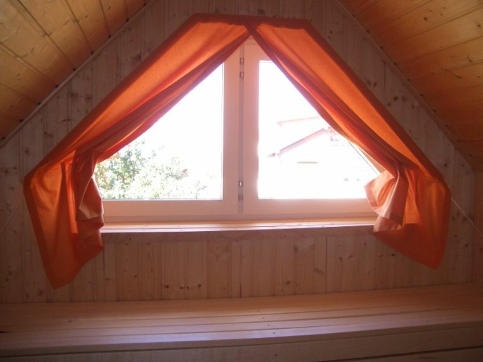 living room curtains ideas, close up of small attic window, surrounded by wooden paneling, decorated with orange red curtains