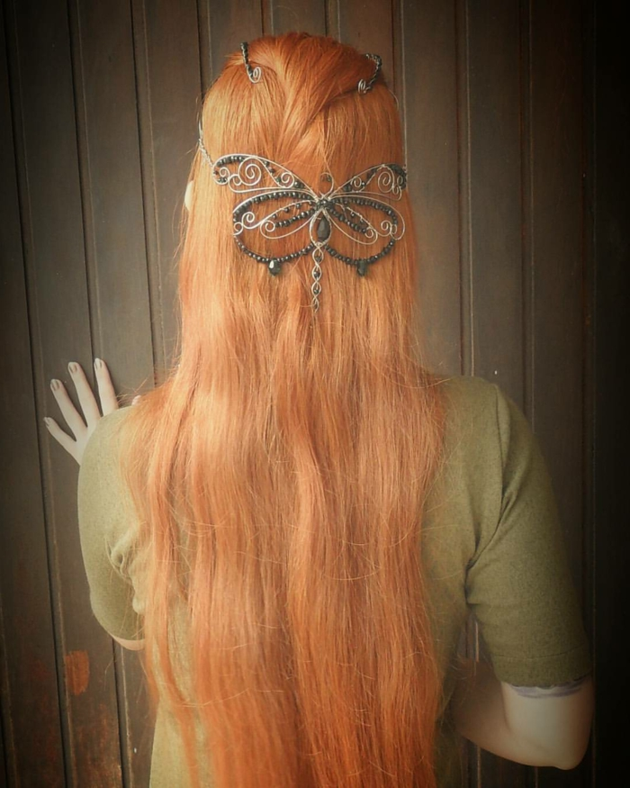 medieval hairstyles, long ginger hair, decorated with a wire butterfly ornament, featuring many black beads, worn by woman in pale, olive green t-shirt