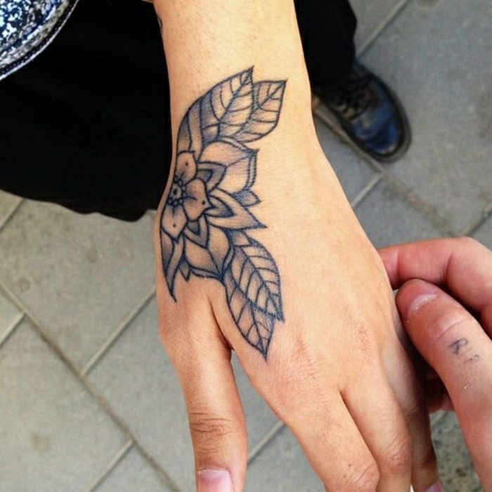 lotus flower tattoo, close up of two hands, one has a simple shaded floral tattoo, done with black ink