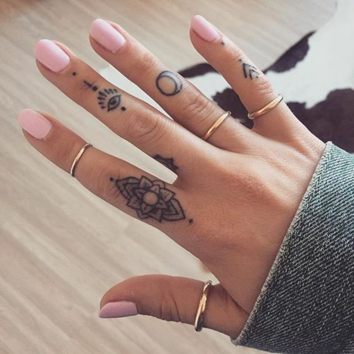 lotus flower tattoo, on a female hand's index finger, all-seeing eye tattoo on her middle finger, moon tattoo on her ring finger, small arrows tattoo on her little finger, pink nail polish, and simple golden rings