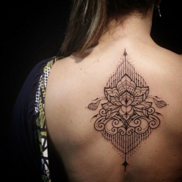 lotus flower tattoo, woman with bare back, and a symmetrical, buddhist lotus tattoo, with swirls and lines, all outlined in black ink