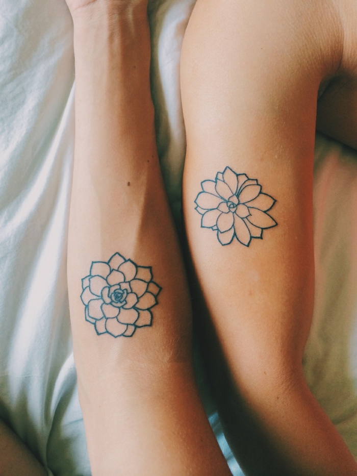 lotus flower tattoo, two bare arms, with similar flower tattoos, outlined with black ink