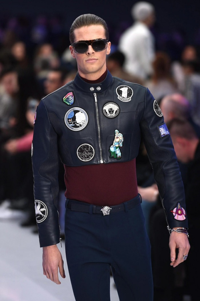 cropped black leather jacket with applique details, worn over maroon top, and skinny navy trousers, by man in dark sunglasses,