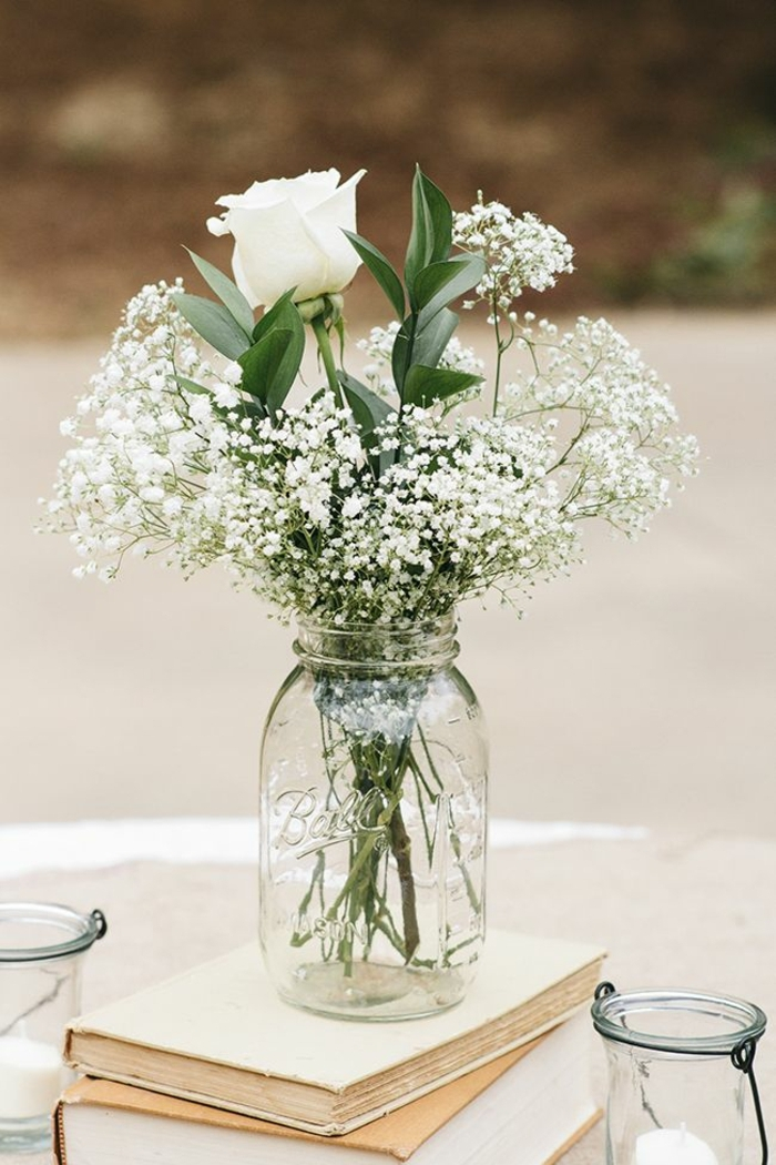mason jar centerpieces, a clear mason jar, placed on stacked beige books, containing a single white rose, green leafy plant, and many tiny white flowers