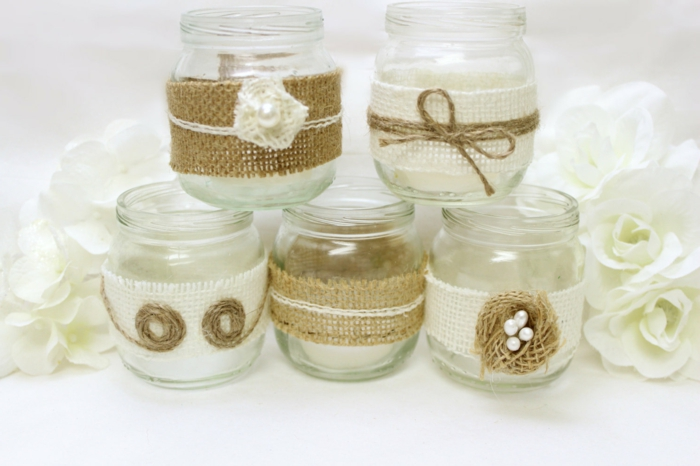 mason jar decorations, five small jars, decorated with white and beige burlap, with string and pearl details, white roses in the background