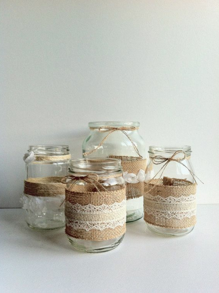 mason jar centerpieces, four different clear jars, decorated with burlap and white lace, each sporting a string bow