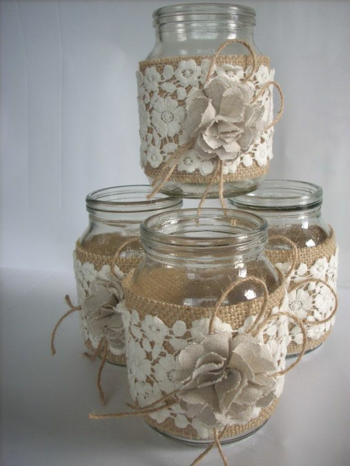 mason jar centerpieces, four identical jars, decorated with white floral lace, placed on top of beige burlap, with burlap flowers and string bows