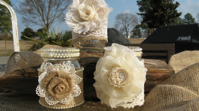 mason jar gifts, three stacked small jars in beige, cream and white, decorated with pearls and lace, with burlap and silk flowers