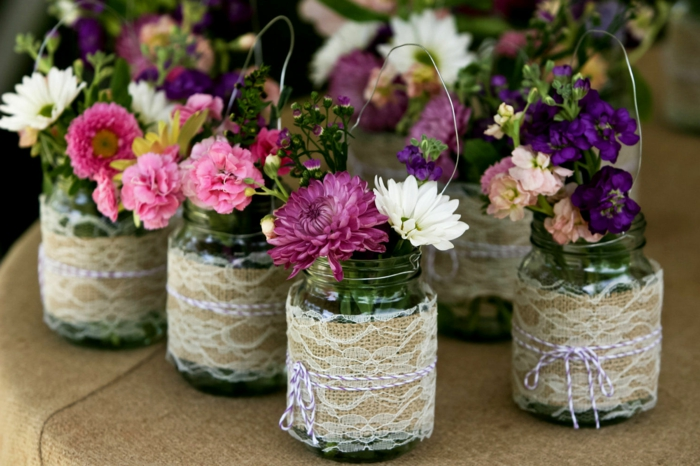 mason jar gifts, several jars with wire handles, decorated with lace over burlap, and two-toned string, containing white and yellow, pink and purple flowers