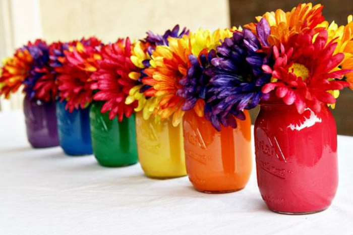 six mason jars, each painted in a different color, purple and blue, green and yellow, orange and pink, containing mixed flowers, in the same colors
