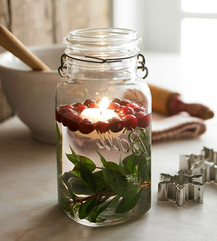 diy mason jar, filled with water, with small twigs with green leaves, cranberries and a lit candle swimming inside