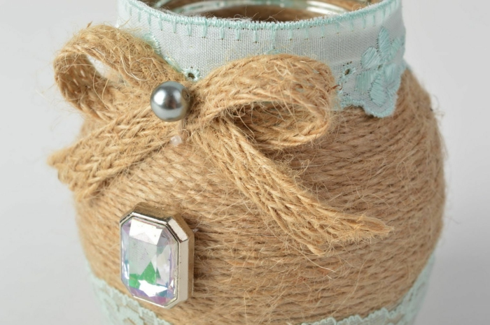 mason jar centerpieces, close up of small jar, decorated with woven string, pale blue ribbon, a silver pearl and a plastic gem