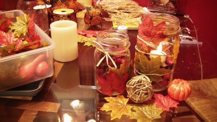 mason jar decorations, two differently sized jars, decorated with autumn leaves in orange and yellow, with candles and leaves, small pumpkins and gourds nearby