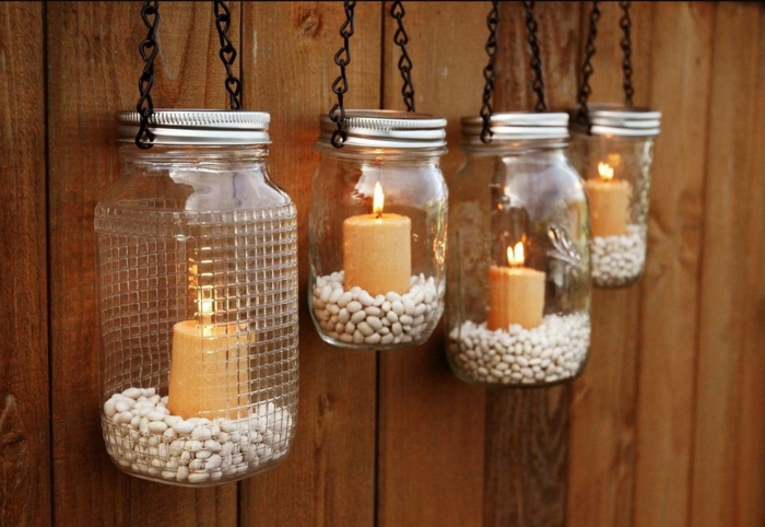 mason jar crafts, four jars with aluminium lids, half-filled with white beans, each containing a lit candle, hanging on black chains, from wooden wall