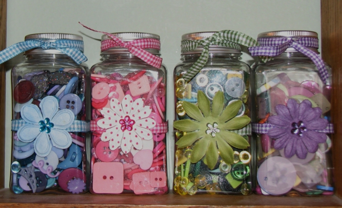 mason jar decorations, four jars decorated in different colors, blue and pink, green and violet, each containing buttons and bands in a corresponding color