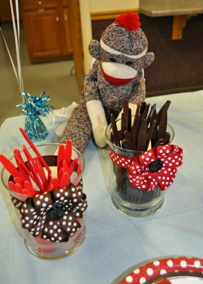 two small jars or glasses, decorated with brown or red ribbon, with bow and polka dots, containing red or brown plastic cutlery, placed on a table, near a stuffed monkey toy