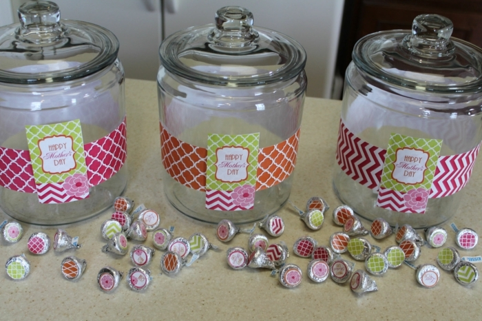 three empty candy jars, with glass lids, decorated with patterned labels in pink and green, orange and white, with many candies, in similarly colored wrappers nearby