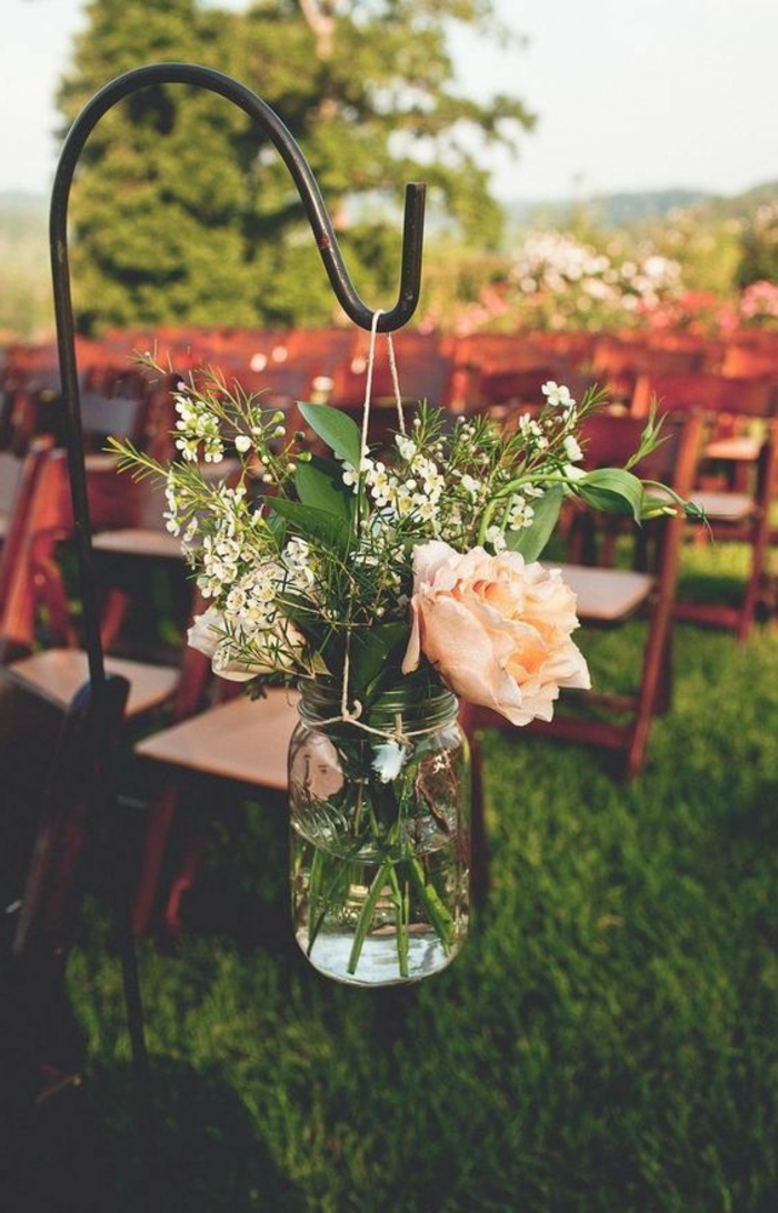 clear jar with string handle, hanging from a metal pole, containing a single pale pink rose, leafy green plants and tiny white flowers, rows of chairs on a meadow in the background