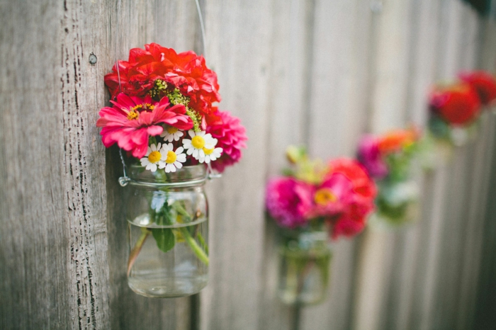 mason jar decorations, clear mason jars with wire handles, hanging from a wooden fence, containing daisies and red flowers