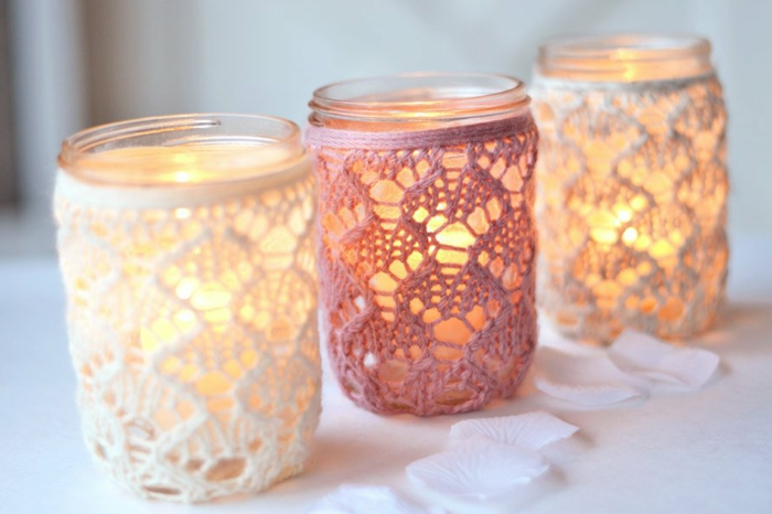 mason jar centerpieces, three jars lit from within, two decorated with white lace, one with pink, white rose petals nearby
