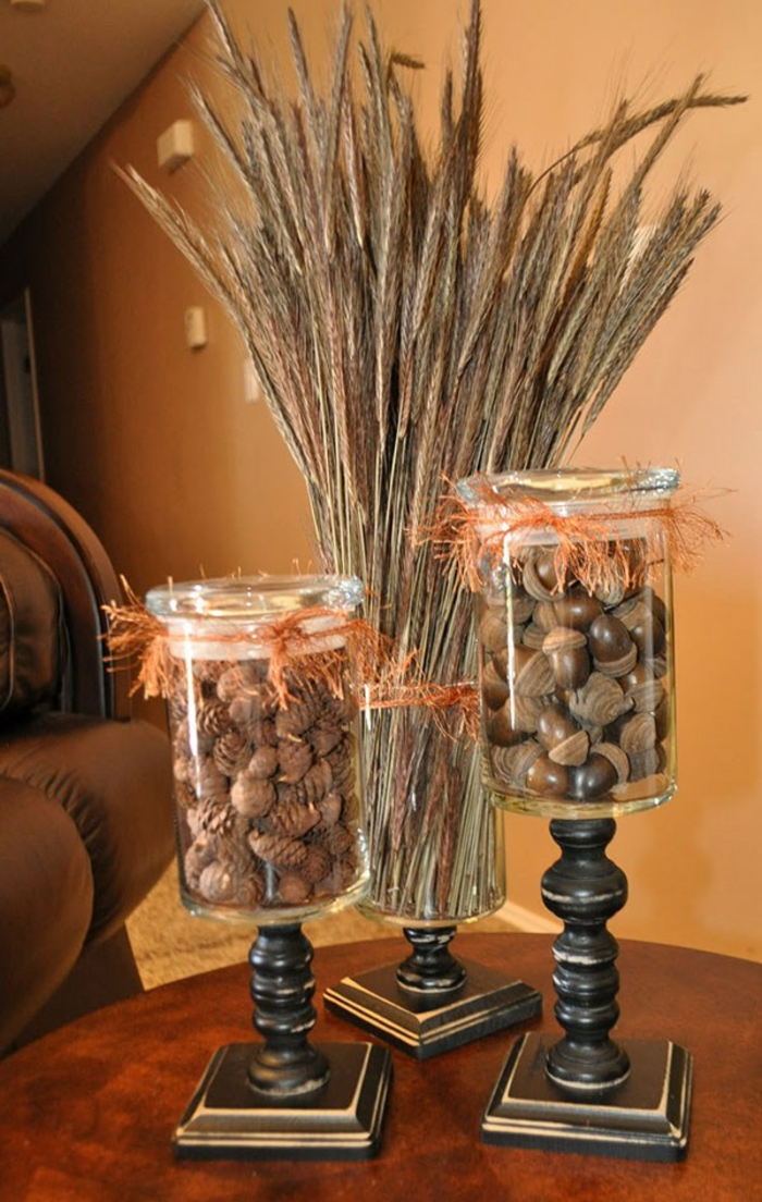 decorating mason jars, three clear jars, stuck to vintage wooden stands, containing tiny fir cones, acorns or a bunch of dried wheat stalks