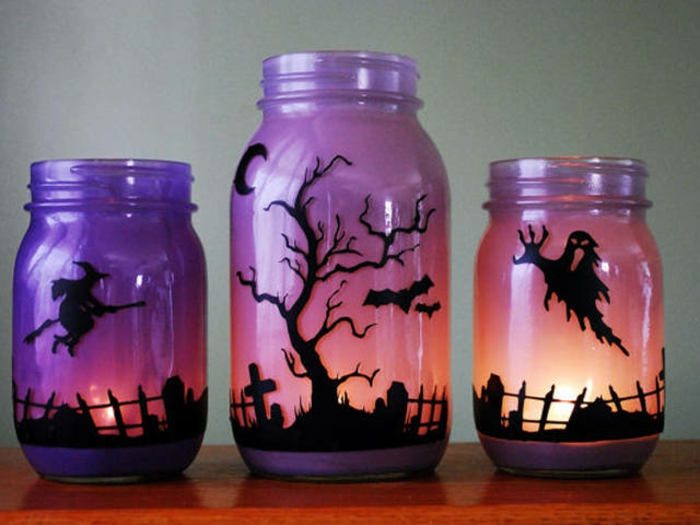 mason jar decorations, one large and two small jars, with lit candles inside, painted to look like an evening sky, with dark silhouettes of a witch, a ghost and a graveyard