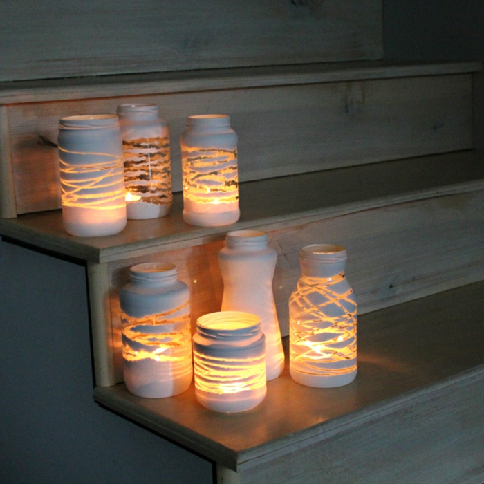 mason jar crafts, seven jars with different shapes and sizes, decorated with white paint in various patterns, and containing lit candles, placed on wooden steps